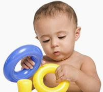 Baby boy playing with toys - stock photo