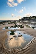 Summer landscape with rocks on beach during late evening and low sunlight Stock Photos