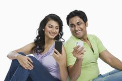 Couple text messaging on mobile phones Stock Photos