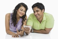 Couple text messaging on mobile phones - stock photo