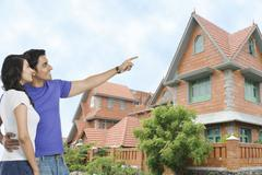 Man standing with his wife and pointing towards a house - stock photo
