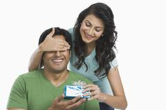 Woman giving a gift to her husband - stock photo