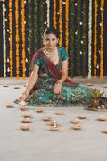 Woman lighting oil lamps on Diwali Stock Photos