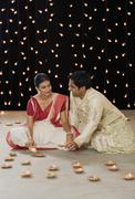 Bengali couple lighting oil lamps Stock Photos