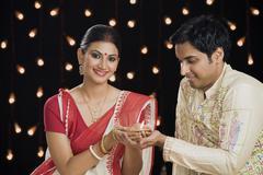Bengali couple holding an oil lamp - stock photo