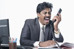 South Indian businessman working in an office and shouting - stock photo