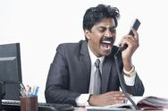 South Indian businessman working in an office and shouting Stock Photos