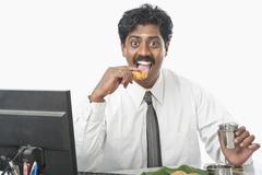 Stock Photo of South Indian businessman working in an office and having food