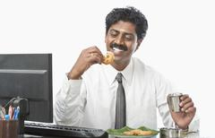 South Indian businessman working in an office and having food - stock photo