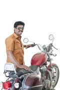 South Indian man standing near a motorcycle Stock Photos