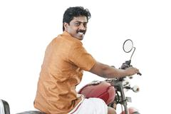 South Indian man riding a motorcycle - stock photo
