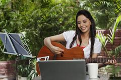 Woman playing a guitar - stock photo