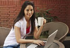 Woman drinking coffee and using a laptop Stock Photos
