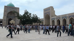 Muslims exit the beautiful Kalon mosque after Friday prayer in Central Asia Stock Footage