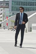 Businessman standing in front of an office building - stock photo