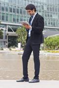 Businessman walking in a garden in front of an office building - stock photo