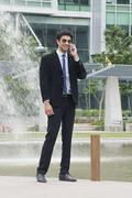 Businessman running in a garden in front of an office building - stock photo