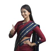 Traditionally Indian woman gesturing thumbs up sign - stock photo