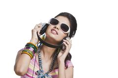Beautiful young woman listening to music on headphones Stock Photos