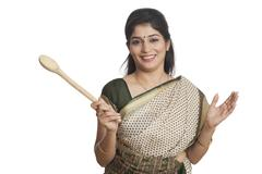 Portrait of a woman holding Wooden ladle - stock photo