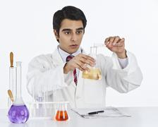 Male scientist doing scientific experiment in a laboratory - stock photo