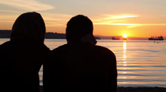 Couple watching sunset at the beach 02 Stock Footage