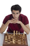 Portrait of a man playing chess and thinking - stock photo