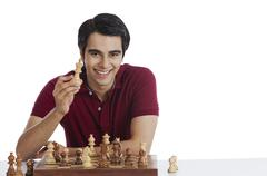 Portrait of a happy man playing chess - stock photo