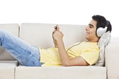 Man lying on a couch and listening to music on a mobile phone Stock Photos