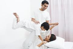 Stock Photo of Happy parents playing with their son on the bed
