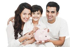 Portrait of a happy family with a piggy bank - stock photo