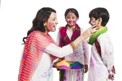 Woman celebrating Holi festival with her children Stock Photos