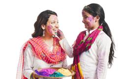Woman celebrating Holi festival with her daughter - stock photo