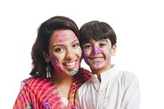 Portrait of a woman with her son celebrating Holi festival Stock Photos