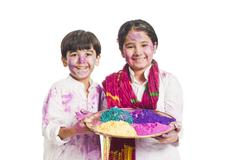 Portrait of brother and sister celebrating Holi festival - stock photo