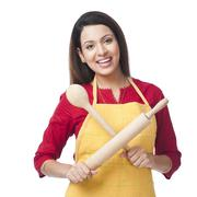 Portrait of a woman holding a rolling pin and ladle - stock photo