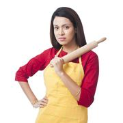 Portrait of a woman holding a rolling pin - stock photo