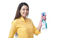 Woman spraying with a cleaning fluid Stock Photos