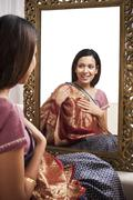Reflection of a woman in mirror trying a sari on herself - stock photo