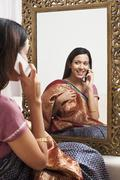 Reflection of a woman in mirror trying a sari on herself and talking on a mobile Stock Photos
