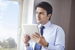Stock Photo of Businessman holding a digital tablet at window