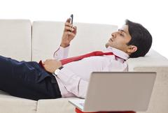 Businessman lying on a couch and using a mobile phone Stock Photos