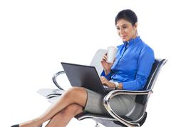 Businesswoman drinking soft drink while using a laptop - stock photo