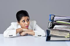 Businesswoman looking at piles of files in an office - stock photo