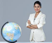 Portrait of a businesswoman standing next to a globe with her arms crossed Stock Photos