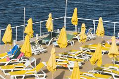 Deck chairs and beach umbrellas at a tourist resort, Malta - stock photo