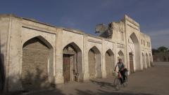 Man cycles past old and crumbled madrassa, Bukhara, Uzbekistan Stock Footage
