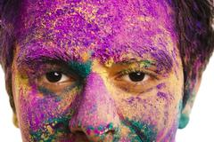 Mans face covered with powder paint during Holi festival - stock photo