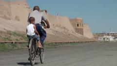 Father and two sons ride around walled Uzbek city Stock Footage
