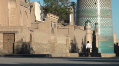 Boy walks through Khiva streets in early morning Stock Footage